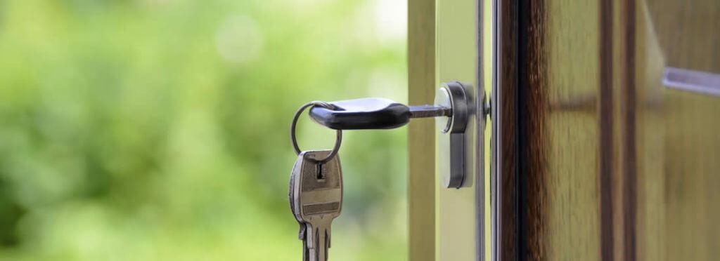 Immobilienkauf - Schlüssel steck in geöffneter Haustür