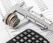Geldmünzen in einem Messschieber mit einem Taschenrechner auf Finanzlisten zum Thema Förderung von Heizungspumpen.